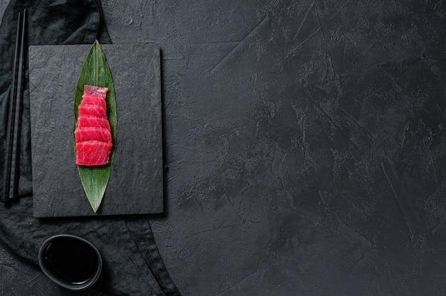 Сашими тунец на каменной доске. черный фон. вид сверху. пространство для текста