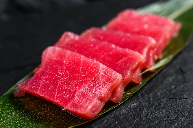Sashimi tuna on a stone board. black background. top view. close up