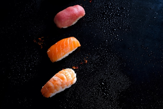 Sashimi, uramaki and nigiri with rice, salmon or tuna, shrimp in black with water drops .