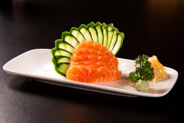 Сашими с лососем в белой тарелке. на черном фоне.