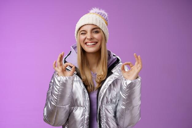 Нахальная привлекательная блондинка в уличной стильной куртке, шляпе с капюшоном, показывает без проблем, ладно, жест совершенства удовлетворен хорошим качеством отеля, широко улыбаясь, широко подмигивая нахальной камерой, наслаждаясь праздниками.