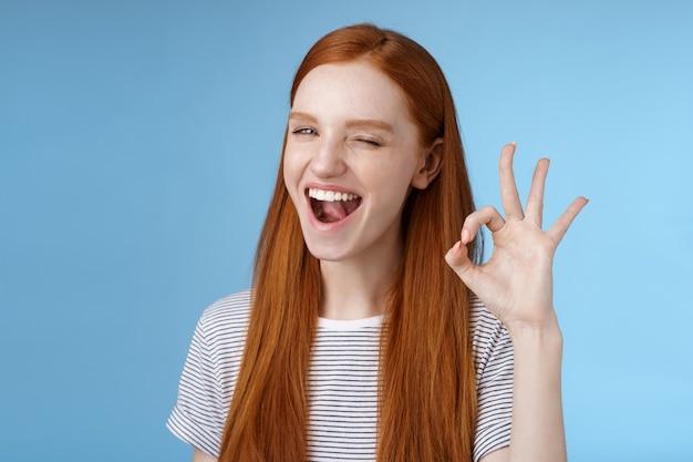 씩씩하고 매력적인 빨간 머리 소녀는 신비스럽게 활짝 웃고 있는 승인 표시를 보여주고 확인 표시를 합니다. 훌륭한 제스처에 만족한 좋은 선택은 훌륭한 결정에 동의하고 기뻐하며 파란색 배경에 서 있습니다.