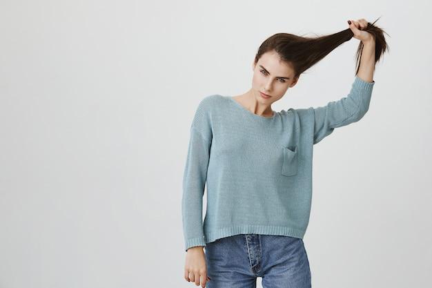 Нахальная привлекательная женщина дергает волосы, рекламирует средства по уходу за волосами