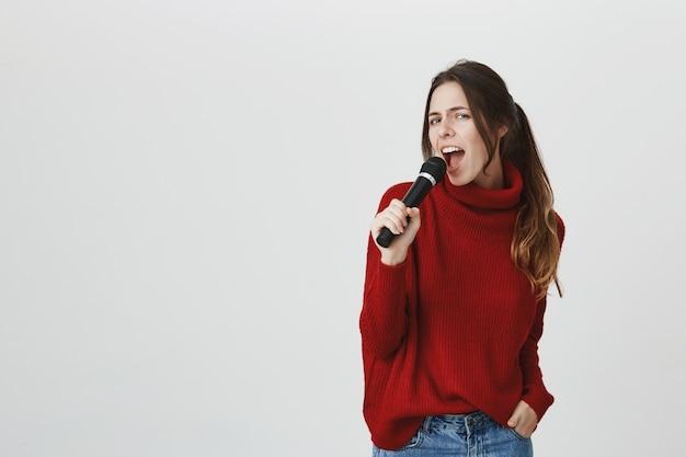 生意気な魅力的な女性がマイクで歌う