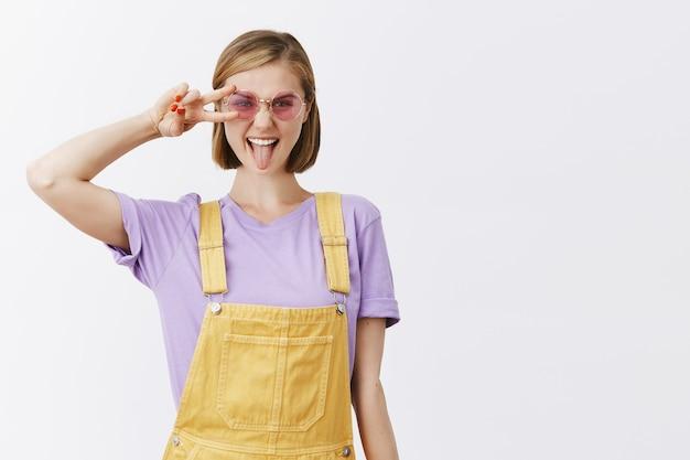Donna attraente impertinente in occhiali da sole alla moda e vestiti estivi che mostrano la lingua e il gesto di pace