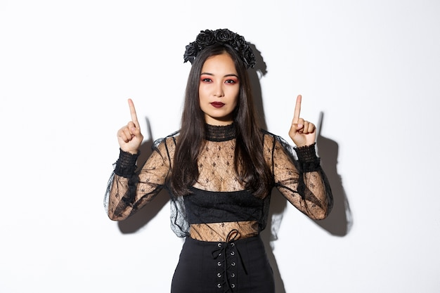 Sassy beautiful asian woman in black gothic dress, wearing witch costume for halloween and pointing fingers up, showing your logo or banner on empty white background, white background.