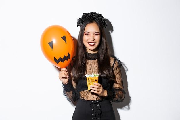 Bella donna asiatica impertinente che gode del dolcetto o scherzetto, che celebra halloween, che tiene palloncino arancione e dolci.