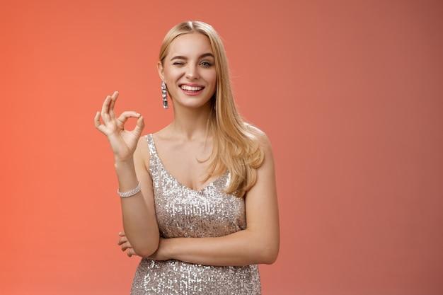 Нахальная белокурая молодая женщина в стильном роскошном серебряном платье, подмигивающая, берет все под контроль, показывает, хорошо, нет проблем, жест делает знак ок, как классная вечеринка, хвалит отличные усилия, красный фон.