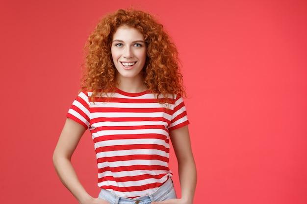 生意気な自信を持って生意気な格好良い赤毛の縮れ毛の女性は、大胆なasserを笑っている手のポケットを保持しています...