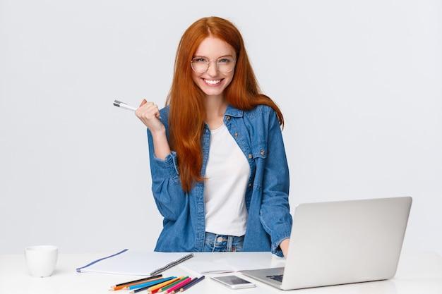 Donna rossa carismatica sfacciata e fiduciosa di bell'aspetto vicino a laptop e tavolo con materiale da disegno, macchina fotografica sorridente sfacciata e mistica, sfondo bianco in piedi con un piano eccellente.