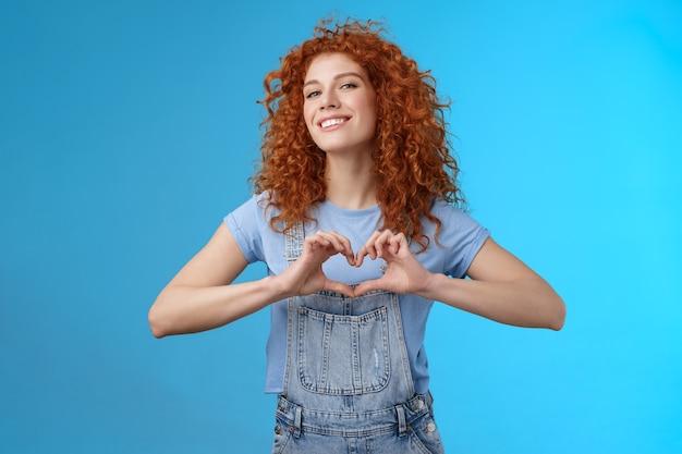 生意気な自信を持って見栄えの良い現代の赤毛の巻き毛の女性は頭を上げる誇り高き愛はガールフレンドにロマンチックな心温まる感情を提示します広く立っている青い背景に笑みを浮かべて自分の心を提示します。