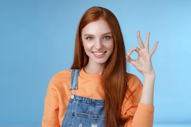 生意気な自信のある赤毛の女の子が制御下に置かれました大丈夫ok優れたジェスチャー生意気な外観カメラニヤリと断定的なすべてが素晴らしい製品、青い背景を承認する許可を与えることを保証します。