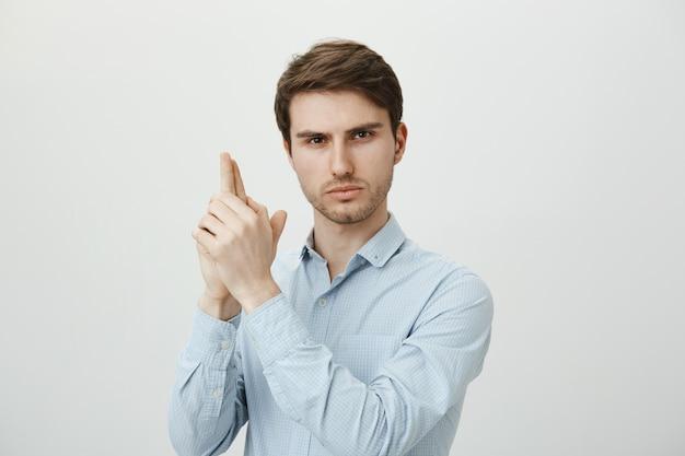 秘密のエージェントを模倣して指銃を示す生意気な自信を持って若い男