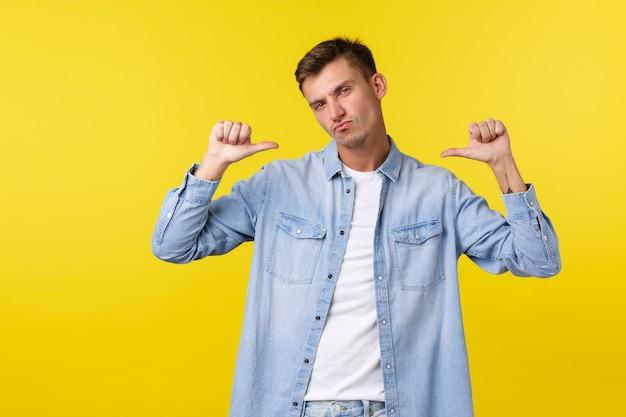 Un bel ragazzo biondo sfacciato e figo che indica se stesso e fa una smorfia, recitando in modo forte e orgoglioso, esibendosi in risultati e obiettivi personali, in piedi su sfondo giallo felice.