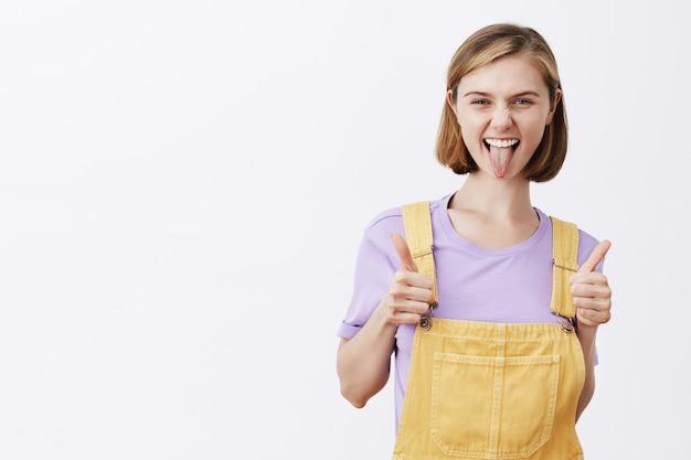 あなたがこれを手に入れたと言っている生意気なかわいいブロンドの女の子は、良い選択を賞賛し、親指を立てて、喜んで笑っています