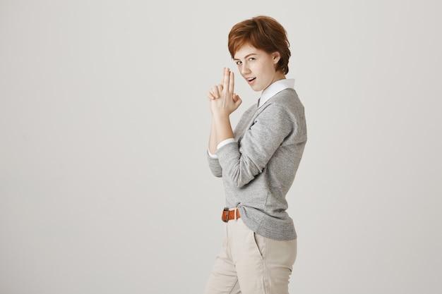 Ragazza rossa impertinente e carina con taglio di capelli corto in posa contro il muro bianco