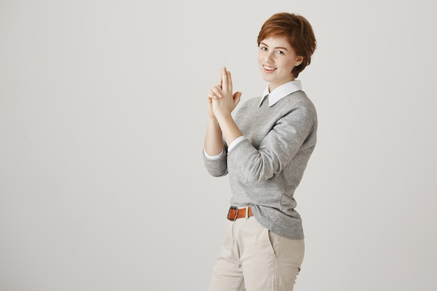 Sassy and cute redhead girl with short haircut posing against the white wall