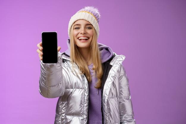 Sassy 기쁘게 쾌활한 금발 여자는 보라색 배경에 서있는 휴대 전화 디스플레이 자랑스럽게 만족스러운 미소 카메라를 보여주는 스마트 폰을 들고 앱 편집 완벽한 사진을 사용하는 것이 좋습니다.