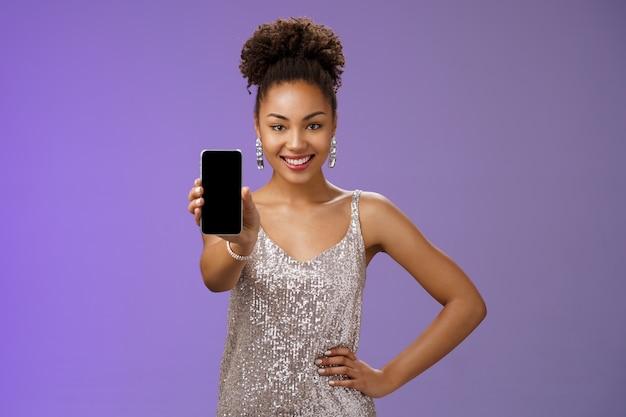 Нахальная элегантная афро-американская женщина в блестящем блестящем серебряном платье держит руку за талию, уверенная поза, с радостью улыбается, протягивает руку, показывая дисплей смартфона, проверяет крутое приложение на синем фоне.