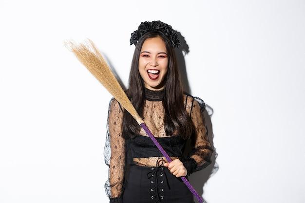 Strega cattiva impertinente ridendo e agitando la sua scopa, indossando il costume di halloween, in piedi su sfondo bianco.