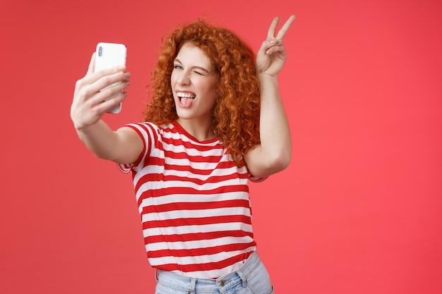 Нахальная модная игривая симпатичная рыжая дерзкая кудрявая женщина показывает мир победе животным ушам жестом ...