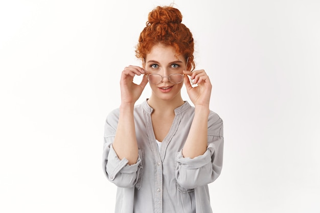 Sassy feminine, caucasian redhead female with curly hair combed bun, wear glasses prepare working, made-up excellent article for blog, smiling assertive, smirk self-assured, feeling like pro