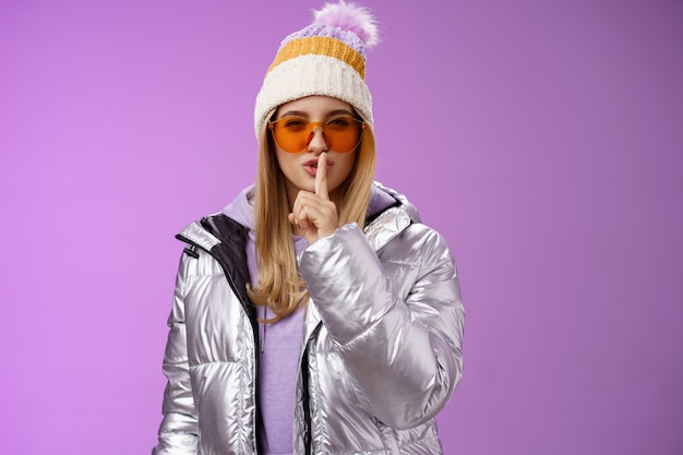 휴가 눈 덮인 산 리조트 착용 겨울 모자 실버 세련된 재킷 선글라스를 즐기는 팬티 꼬리 치는 화려한 여자