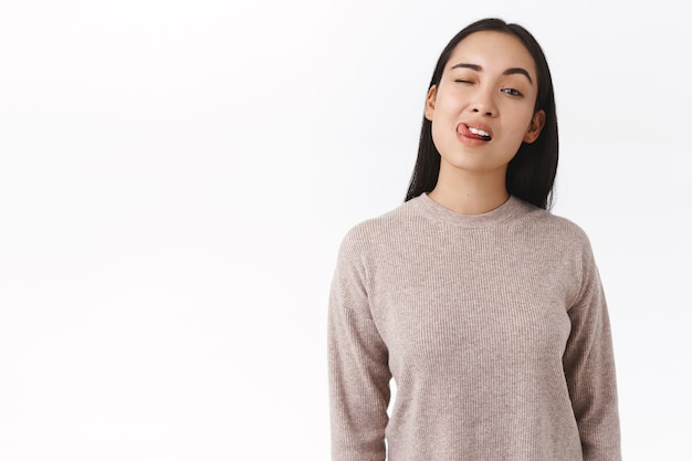 Sassy, flirty attraente donna asiatica che mostra il suo flirt abile, strizzando l'occhio e mostrando la lingua civettuola, cercando di sedurre qualcuno o chiedere il numero di telefono, la donna è venuta al bar lgbt per la prima volta, muro bianco