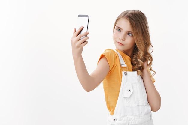 生意気な魅力かわいい金髪のかわいい女の子がスマートフォンを持って、女性的で愚かなポーズをとる自撮り写真を撮り、自信を持って凝視し、大人の女性を模倣し、白い壁に立つ