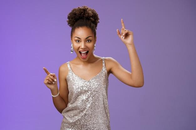Нахальная симпатичная афроамериканка в модном гламурном серебряном блестящем платье указательные пальцы подняли вверх улыбающиеся, дерзкие, радостно празднующие отличные счастливые новости, танцующие с ухмылкой, стоя на синем фоне.