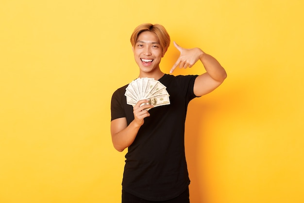 Sassy good-looking korean blond guy, smiling happy and pointing finger at money, winning cash, standing yellow wall
