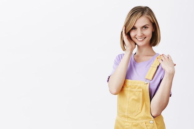 生意気な格好良い若い女性が散髪を修正し、コケティッシュに見える