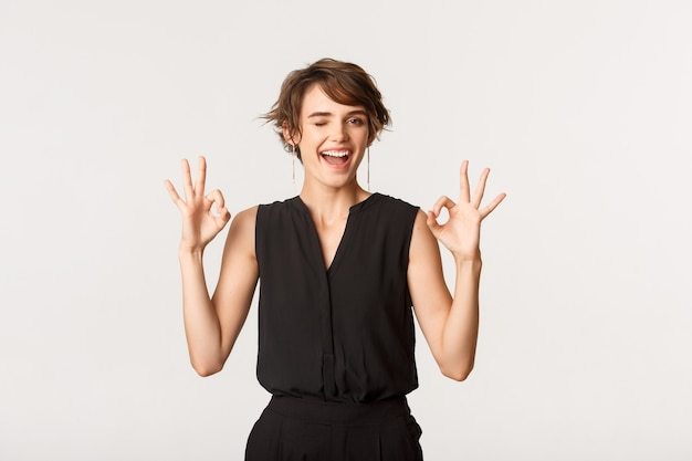 Sassy good-looking young woman assure you, showing okay gesture