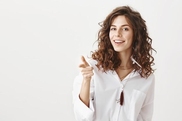 生意気なゴージャスな女性の笑顔、指を指す
