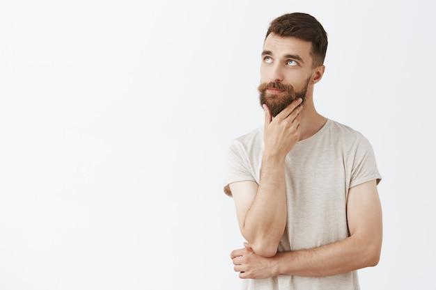 Uomo barbuto bello impertinente che posa contro il muro bianco