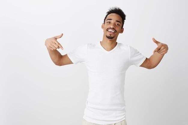 Sassy e bell'uomo dalla pelle scura che punta il dito verso il basso, mostrando promo, invitando il link al clic