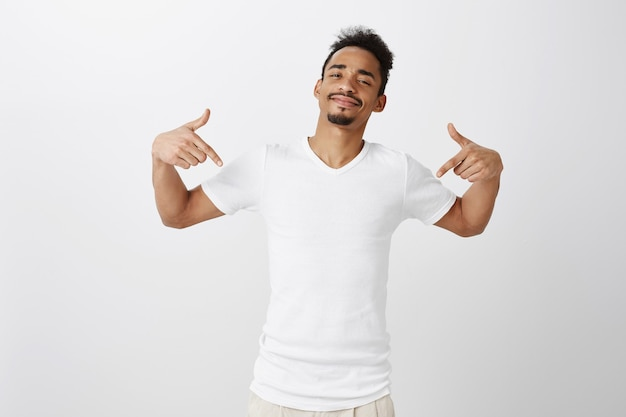 Sassy and handsome dark-skinned man pointing fingers down, showing promo, inviting click link