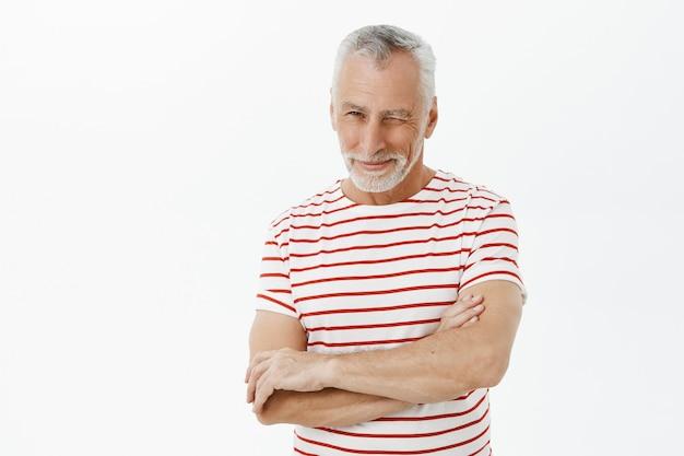 Uomo anziano bello impertinente che sbatte le palpebre incoraggiante