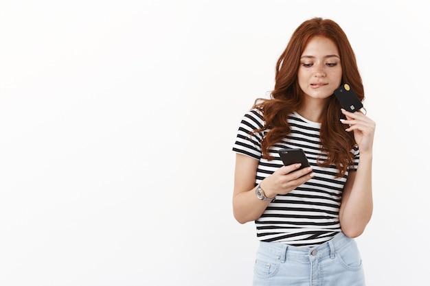 生意気な現代のかわいい若い赤毛の女の子がオンラインショップをスクロールし、スマートフォンを持ち、誘惑から唇を噛み、何を買うかを考え、クレジットカードを持ち、モバイル画面を思慮深く見つめる、白い壁