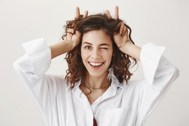 Donna giocosa impertinente sorridente e ammiccante, mostrando le corna sopra la testa