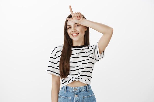 Sassy and pleased girl who won showing loser gesture over forhead, mocking lost team