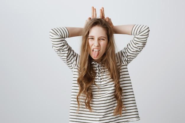 Нахальная красивая девушка подмигивает и показывает жест и язык кроличьих ушей