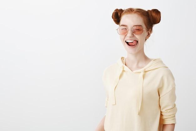 舌を示すスタイリッシュなサングラスで生意気な赤毛の女の子