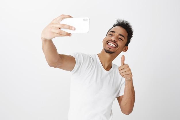 Нахальный улыбающийся афро-американский парень, делающий селфи на смартфоне и показывающий жест пальца вверх