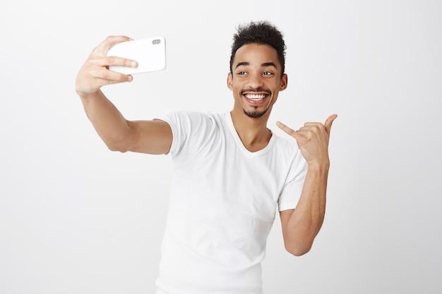 Sassy sorridente ragazzo afro-americano prendendo selfie sullo smartphone, mostrando il gesto di yolo