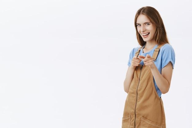 Donna attraente sorridente impertinente che punta il dito, complimenti, gesto ben fatto, elogiando un'ottima scelta