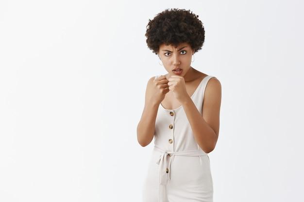 Ragazza alla moda impertinente che posa contro il muro bianco