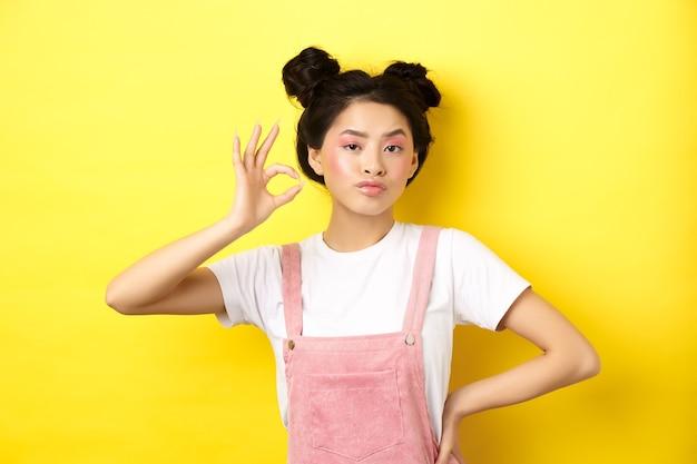 밝은 핑크색 화장과 콧대가 높은 십대 아시아 소녀, 괜찮아 기호 표시 및 승인에 끄덕임, 심각한 얼굴, 나쁜 제스처가 아닌 노란색 반대 서있는 제품을 승인하십시오.