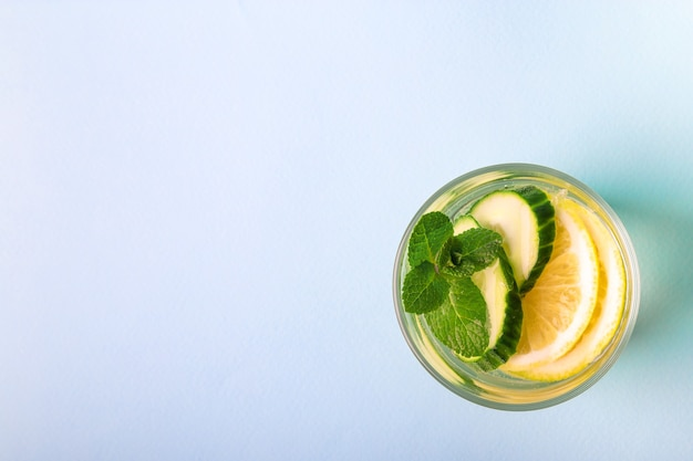 Sassy water for detox infused with lemon, cucumber and mint in glass on light blue background. top view. healthy lifestyle concept. space for text.