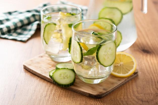 生意気な水または木製のテーブルにキュウリとレモンの水